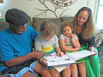 """""""Reading is a big part of the quality time we spend together,"""" says Tom Reynolds (left) as granddaughter Chloe (center) reads to her sister Chelsea, and grandmother Cathy.    Photo: Urban News"""