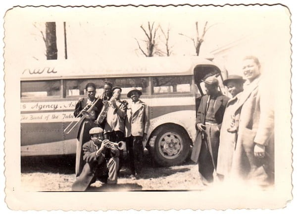 Members of the Sax Kari Orchestra from Detroit pose in front of the  Mason James Agency's tour bus. Taken in Ft. Smith, Arkansas, March 1947.
