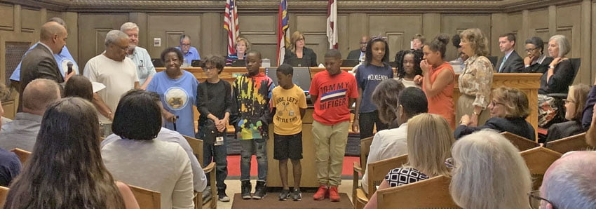 Ms. Sophie Dixon stands with youth from Asheville's Shiloh community as she is presented the  Volunteer of the Year Award by members of Asheville City Council.