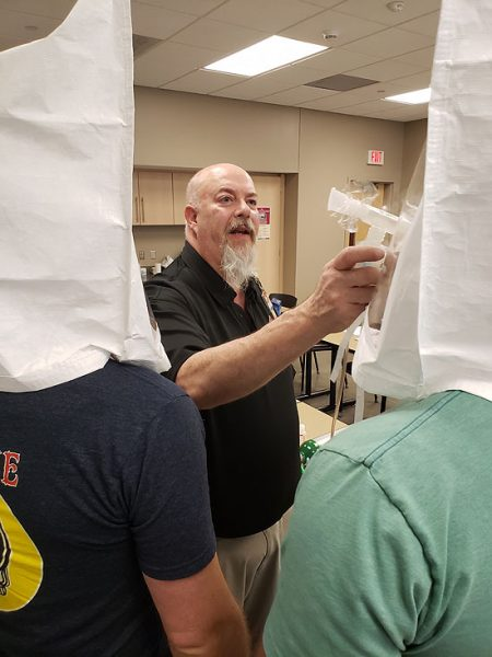 A-B Tech EMS Chair Anthony Green tests the fit of protective face masks for local first responders.