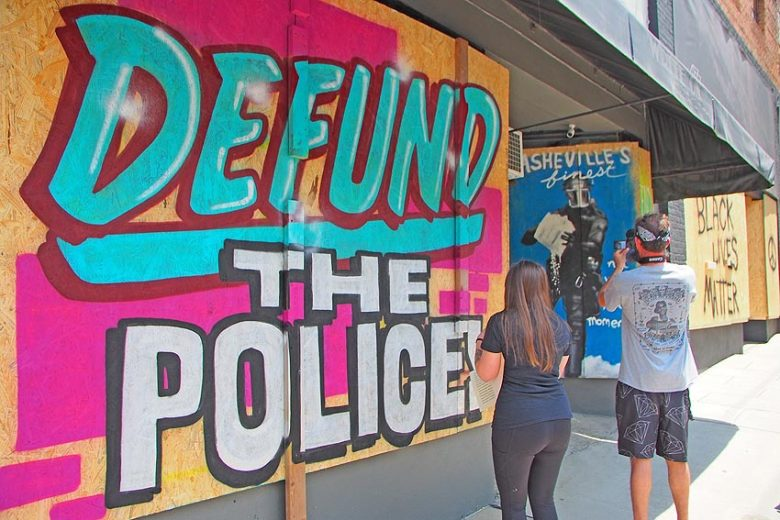 defund police artwork on boarded up window
