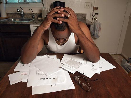 worried over bills man holds head in hands