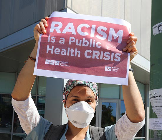 nurse holding racism health crisis sign
