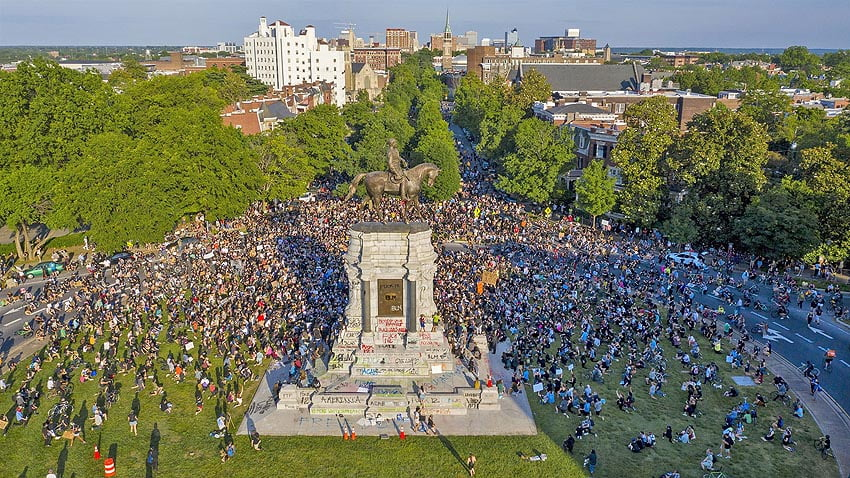 Statue of Robert E Lee in Richmond, Virginia surrounded by crowd.
