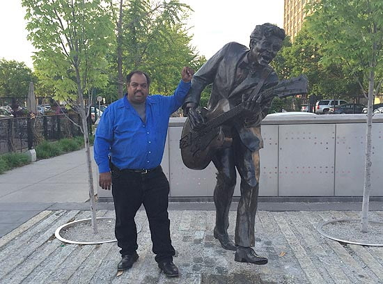 Blues musician Daryl Davis next to statue of Chuck Berry in St Louis