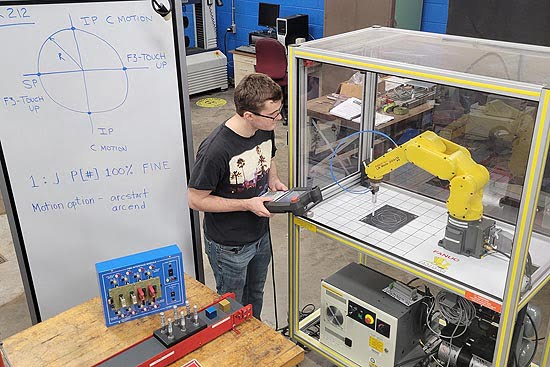 A student tests an automated, servo-mechanical system.
